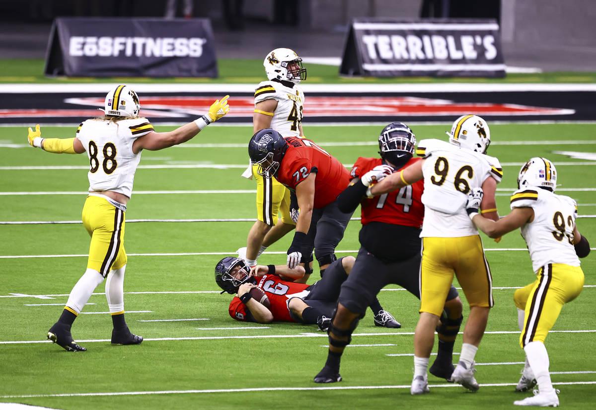 UNLV Rebels offensive lineman Matt Brayton (72) looks to help up UNLV Rebels quarterback Max Gi ...