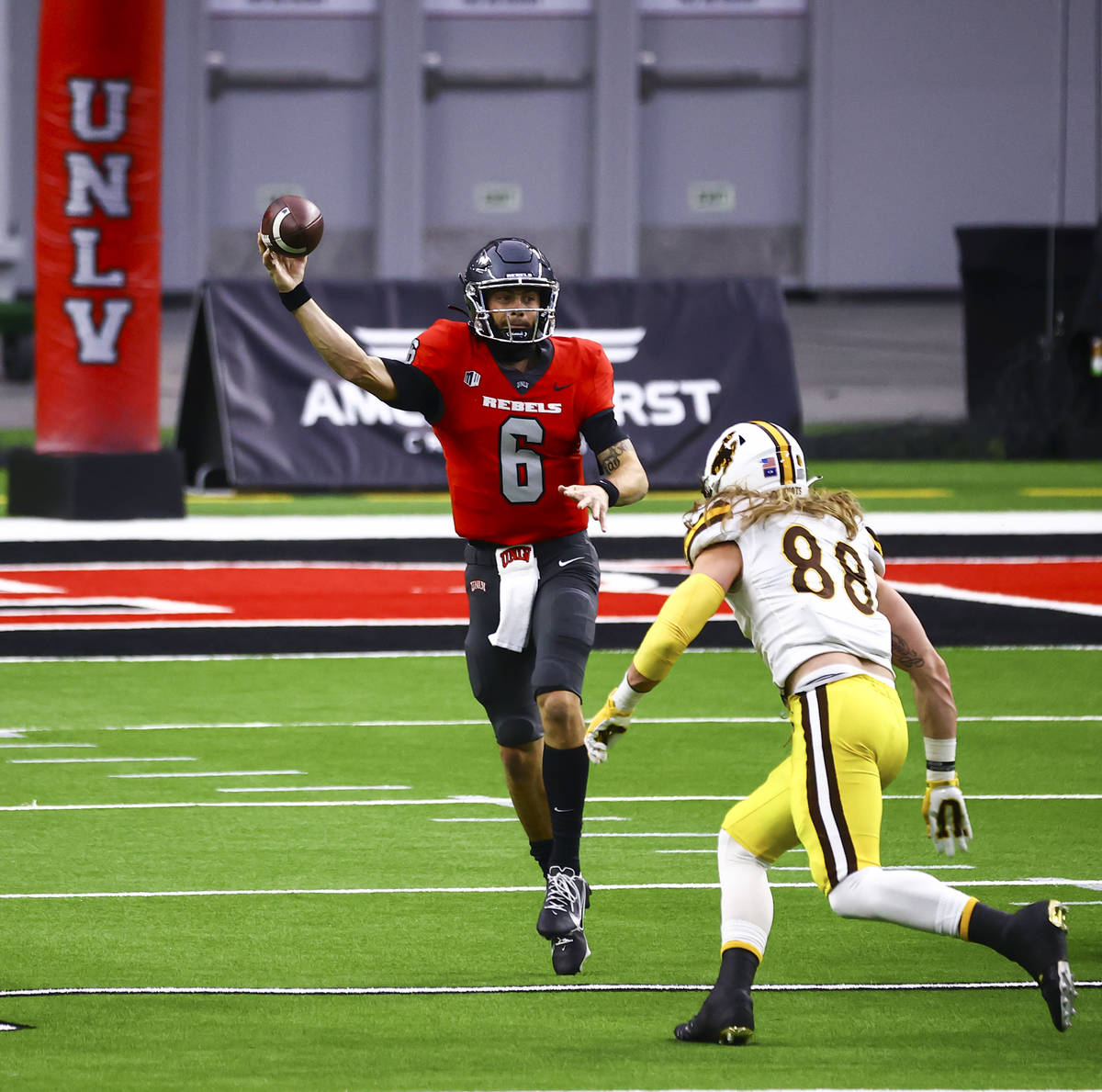 UNLV Rebels quarterback Max Gilliam (6) looks to throw under pressure from Wyoming Cowboys defe ...
