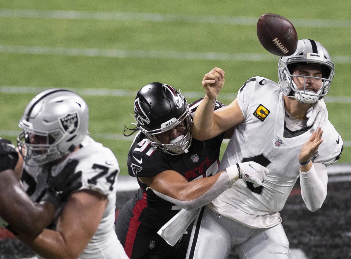 Las Vegas Raiders quarterback Derek Carr (4) is strip sacked by Atlanta Falcons defensive tackl ...