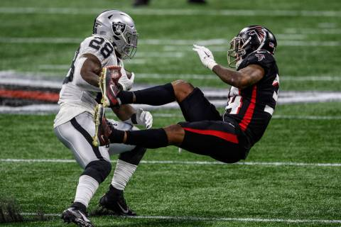 Atlanta Falcons defensive back Darqueze Dennard (34) is hit by Las Vegas Raiders running back J ...
