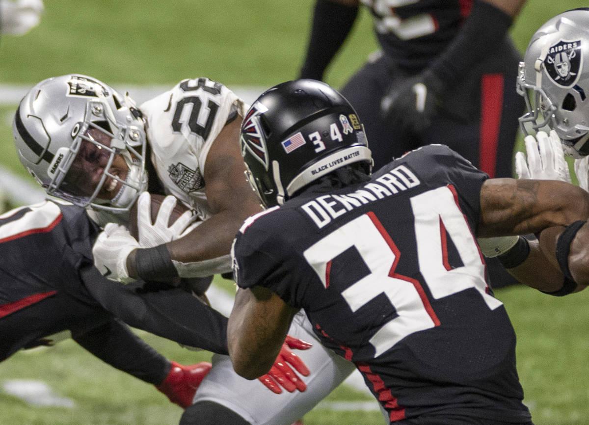 Las Vegas Raiders running back Josh Jacobs (28) is tackled by Atlanta Falcons cornerback Darque ...