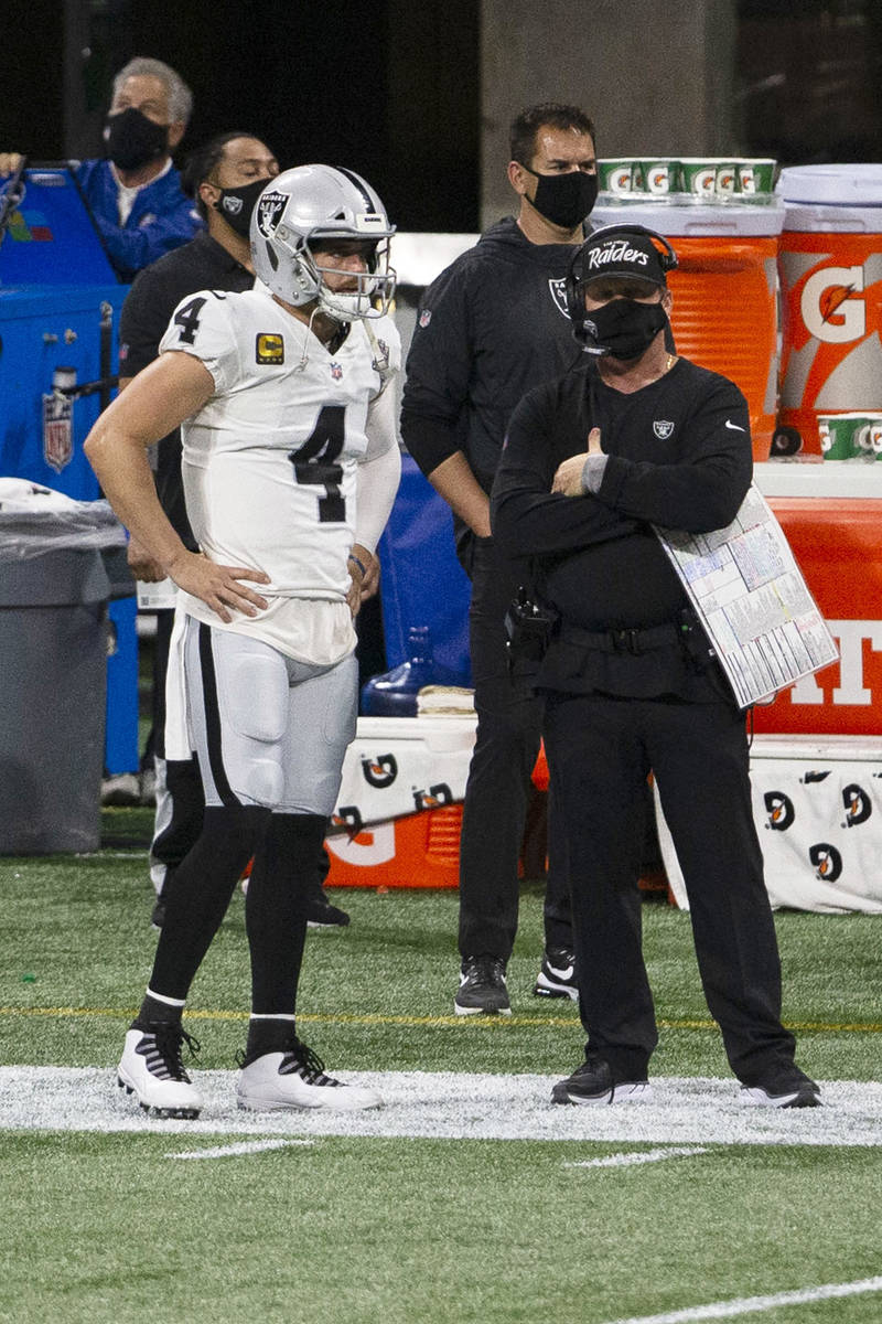 Las Vegas Raiders quarterback Derek Carr (4) and head coach Jon Gruden look on from the sidelin ...