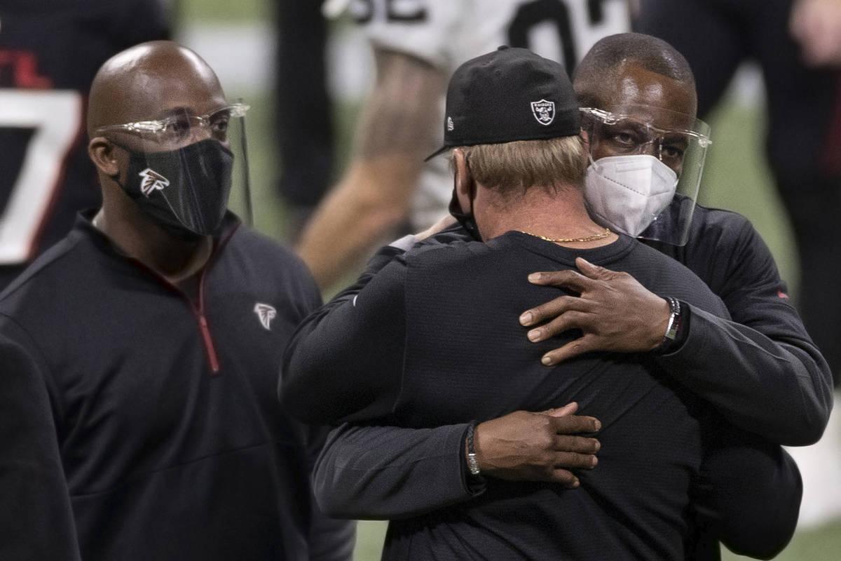 Atlanta Falcons head coach Raheem Morris, right, hugs Las Vegas Raiders head coach Jon Gruden a ...