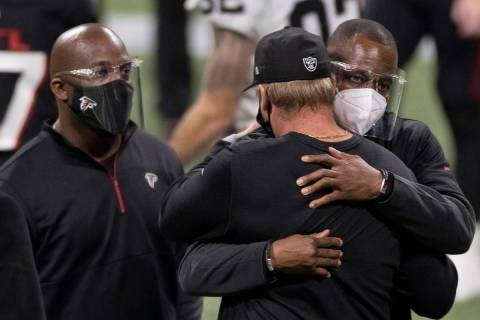 Atlanta Falcons head coach Raheem Morris, right, hugs Las Vegas Raiders head coach Jon Gruden a ...