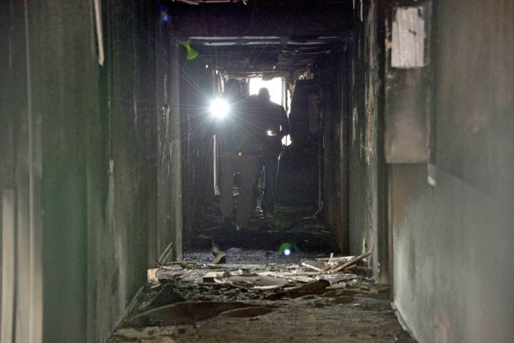 Investigators walk through an interior corridor Dec. 21, 2019 after an early-morning fire at th ...