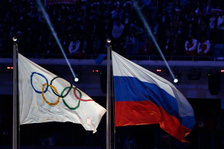 In this Feb. 23, 2014, file photo the Russian national flag, right, flies after it is hoisted n ...