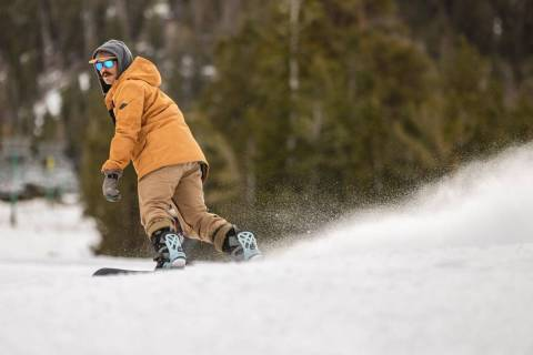 Snowboarder Ian Ryan of Las Vegas glides down the run near the lodge during opening day of skii ...