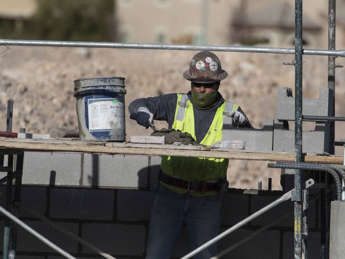 A construction worker lays blocks at the underground parking garage at the Evora apartment comp ...