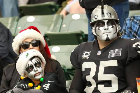 A family of Oakland Raiders fans watch the team play against the Los Angeles Chargers during th ...