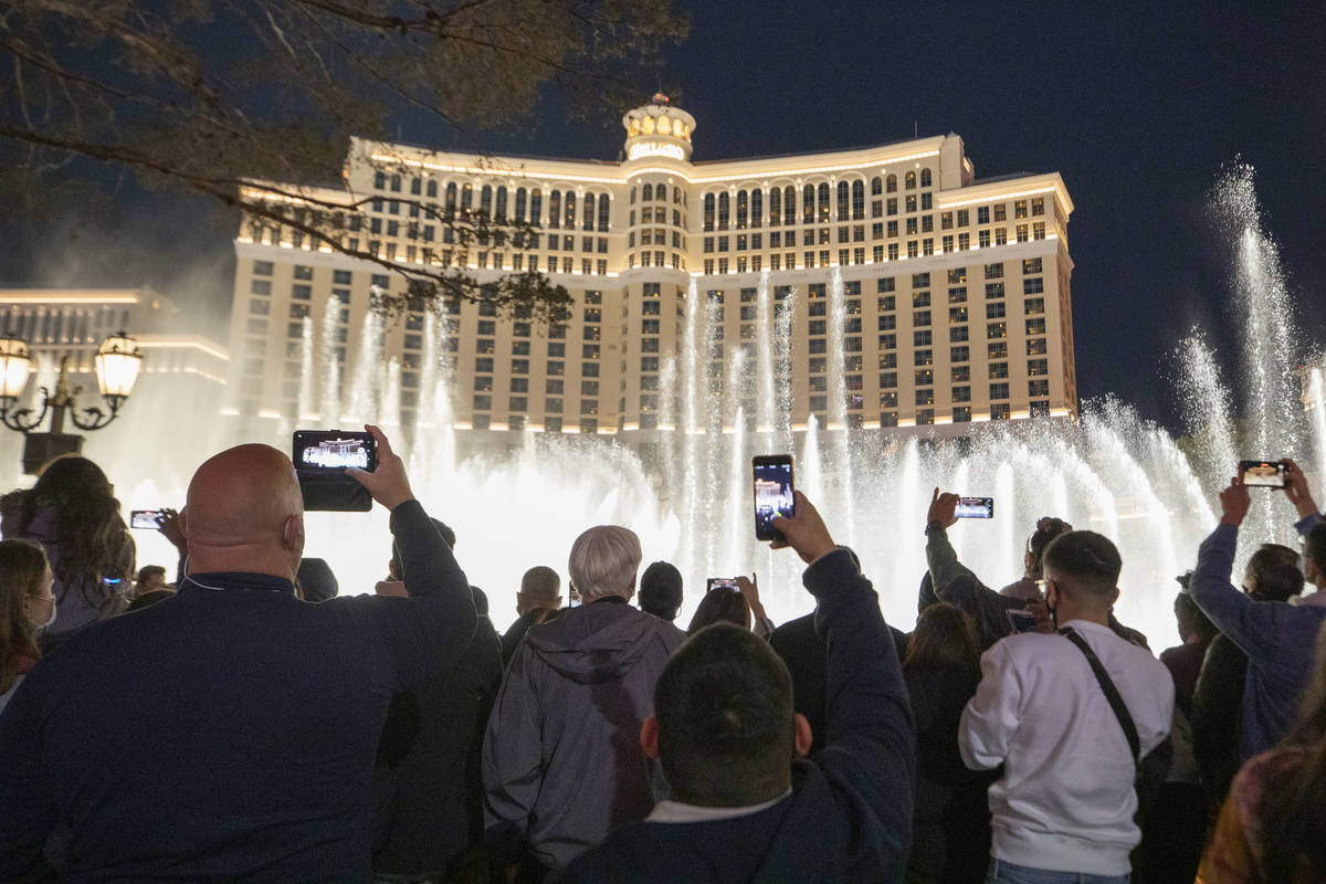 Individuals watch the Bellagio Fountains while celebrating New Years Eve on the Las Vegas Strip ...
