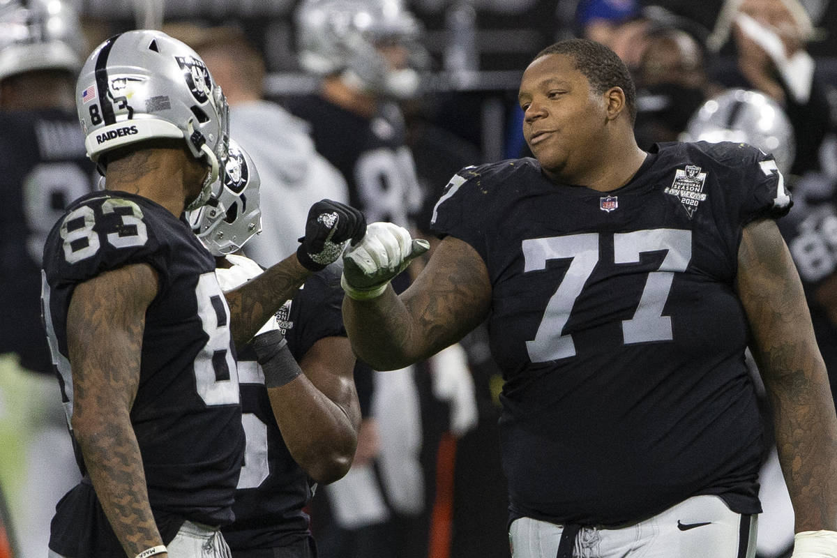 Raiders offensive tackle Trent Brown (77) fist bumps Raiders tight end Darren Waller (83) in th ...