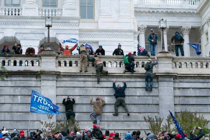 Supporters of President Donald Trump climb the west wall of the the U.S. Capitol on Wednesday, ...