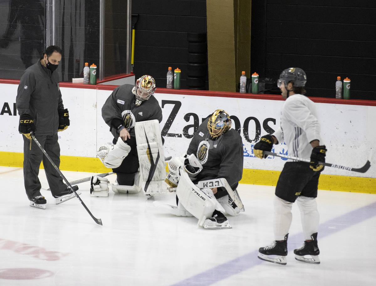 Golden Knights goalie coach Mike Rosario, left, talks with Golden Knights goaltenders Robin Leh ...