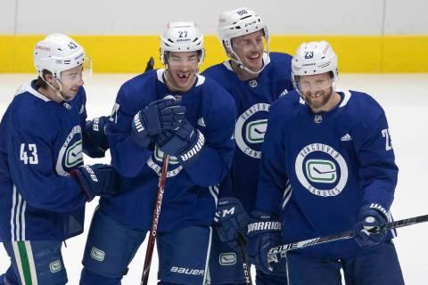 From left to right, Vancouver Canucks defensemen Quinn Hughes, Travis Hamonic, Nate Schmidt and ...