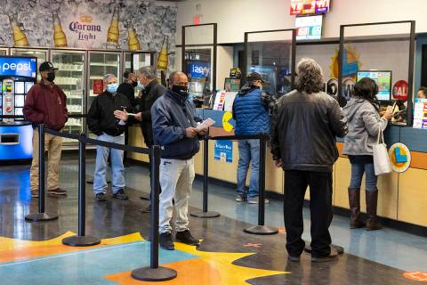 People line up inside of the Prime Valley Lotto Store as they wait to buy the Mega Million and ...
