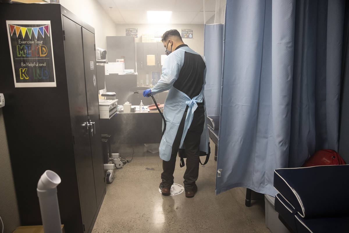 School custodian Gabriel Gonzalez sprays the nurse's office with a sanitizer at Mater Academy E ...