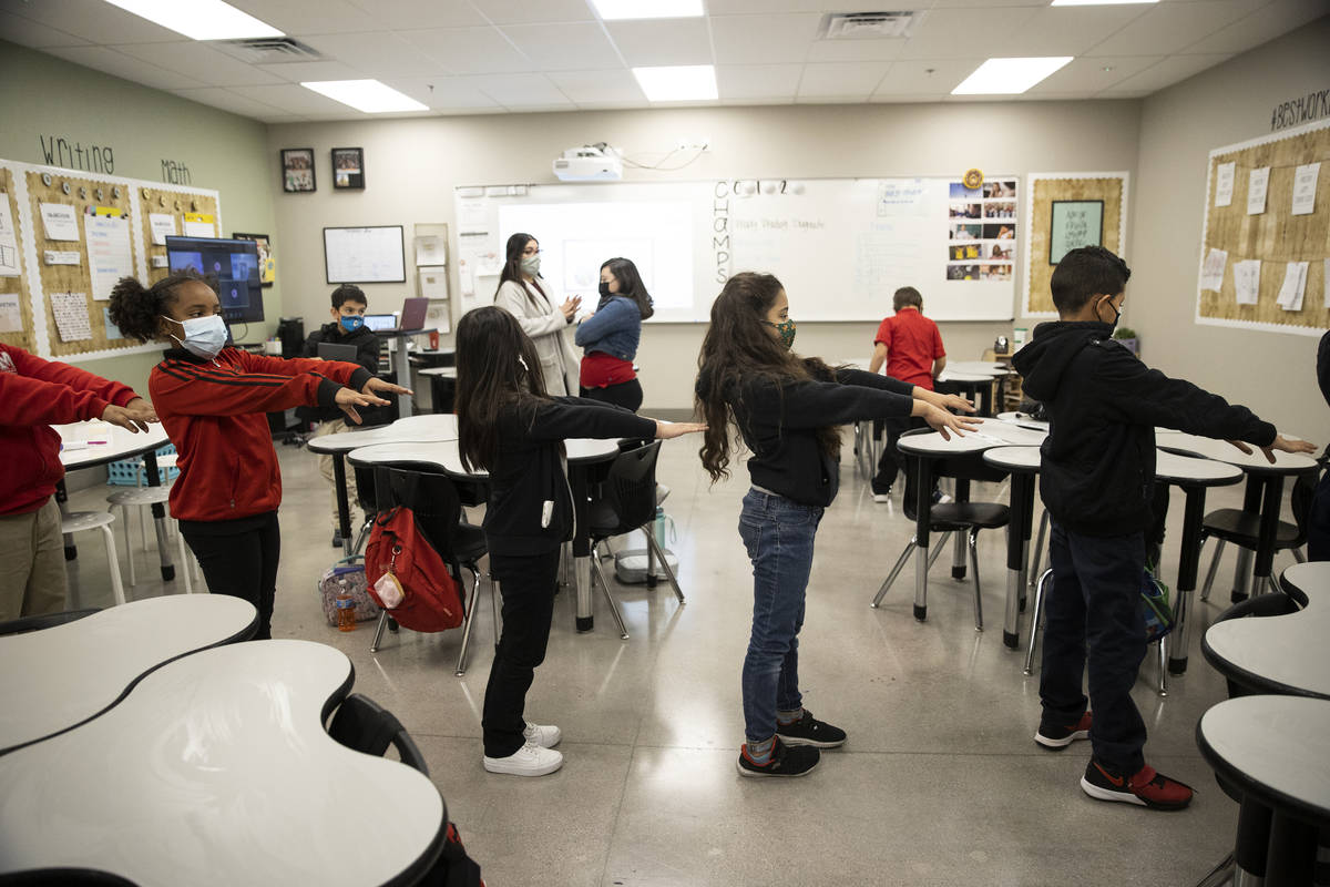 Students reach out with their arms to practice social distancing while walking to their next cl ...