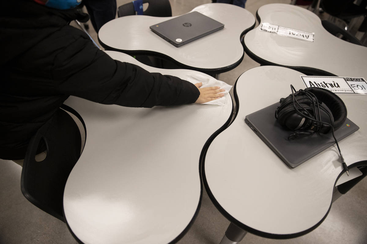 A student wipes down his desk at the end of his class at Mater Academy East Campus in Las Vegas ...