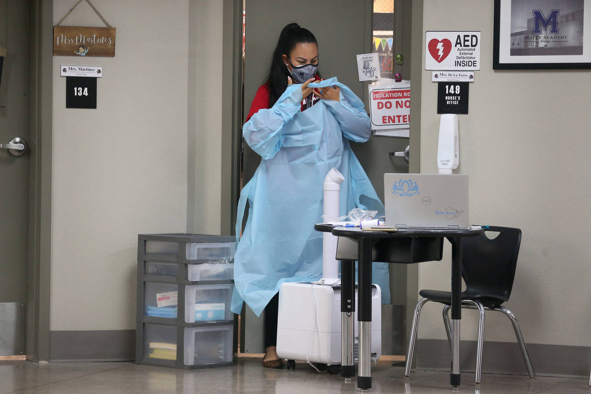School nurse Kenia Delatorre wears personal protection equipment before sanitizing her office a ...