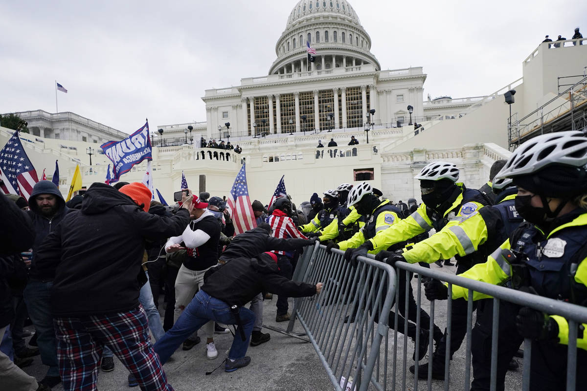 FILE - In this Jan. 6, 2021, file photo, Trump supporters try to break through a police barrier ...