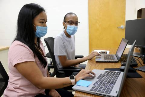 April Cruda, left, trains fellow UNLV student Alliyah Jackson on the school's COVID-19 contact ...