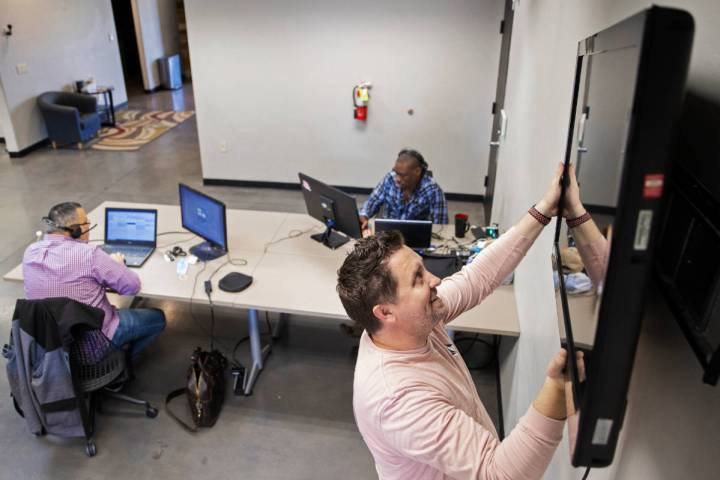 Kenny Eliason, co-owner of Work in Progress, removes a television from the wall during the busi ...