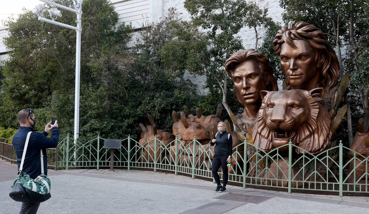 John Hayton of Chicago takes a photo of his wife Stacy Hayton in front of a statue of Siegfried ...