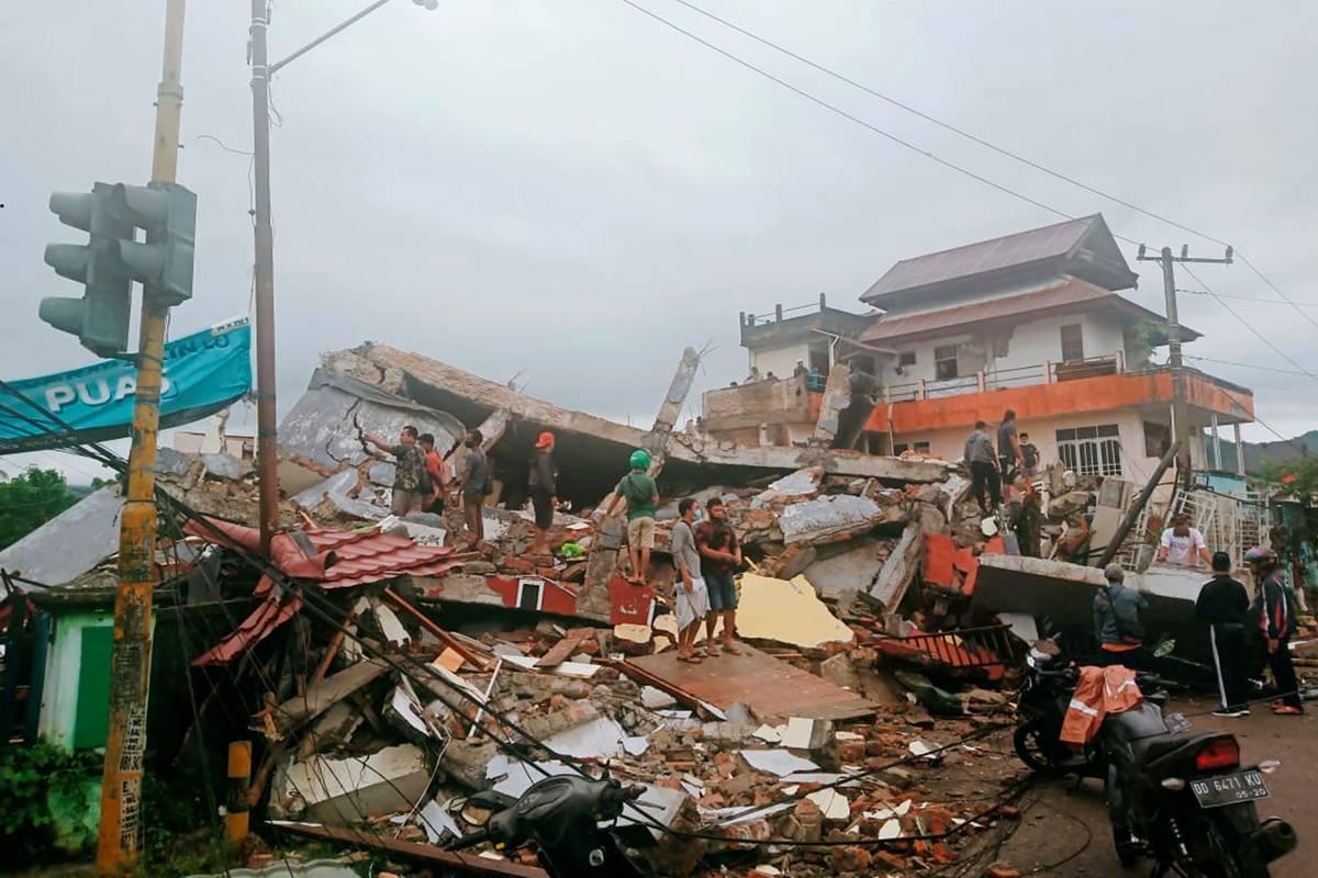 Residents inspect earthquake-damaged buildings in Mamuju, West Sulawesi, Indonesia, Friday, Jan ...