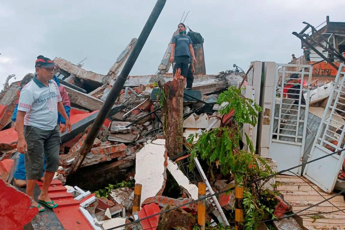 Residents inspect earthquake-damaged houses in Mamuju, West Sulawesi, Indonesia, Friday, Jan. 1 ...