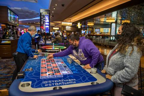 Marvin Alvarez, center, lays down more chips on a Roulette table next to girlfriend Celia Gamer ...