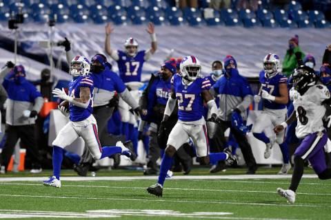 Buffalo Bills cornerback Taron Johnson, left, runs away from Baltimore Ravens quarterback Lamar ...