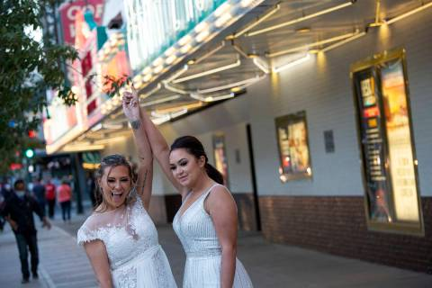 Newlyweds Brittnee Austin, left, and Kirby Kraeymer-Austin pose for their wedding photographer, ...