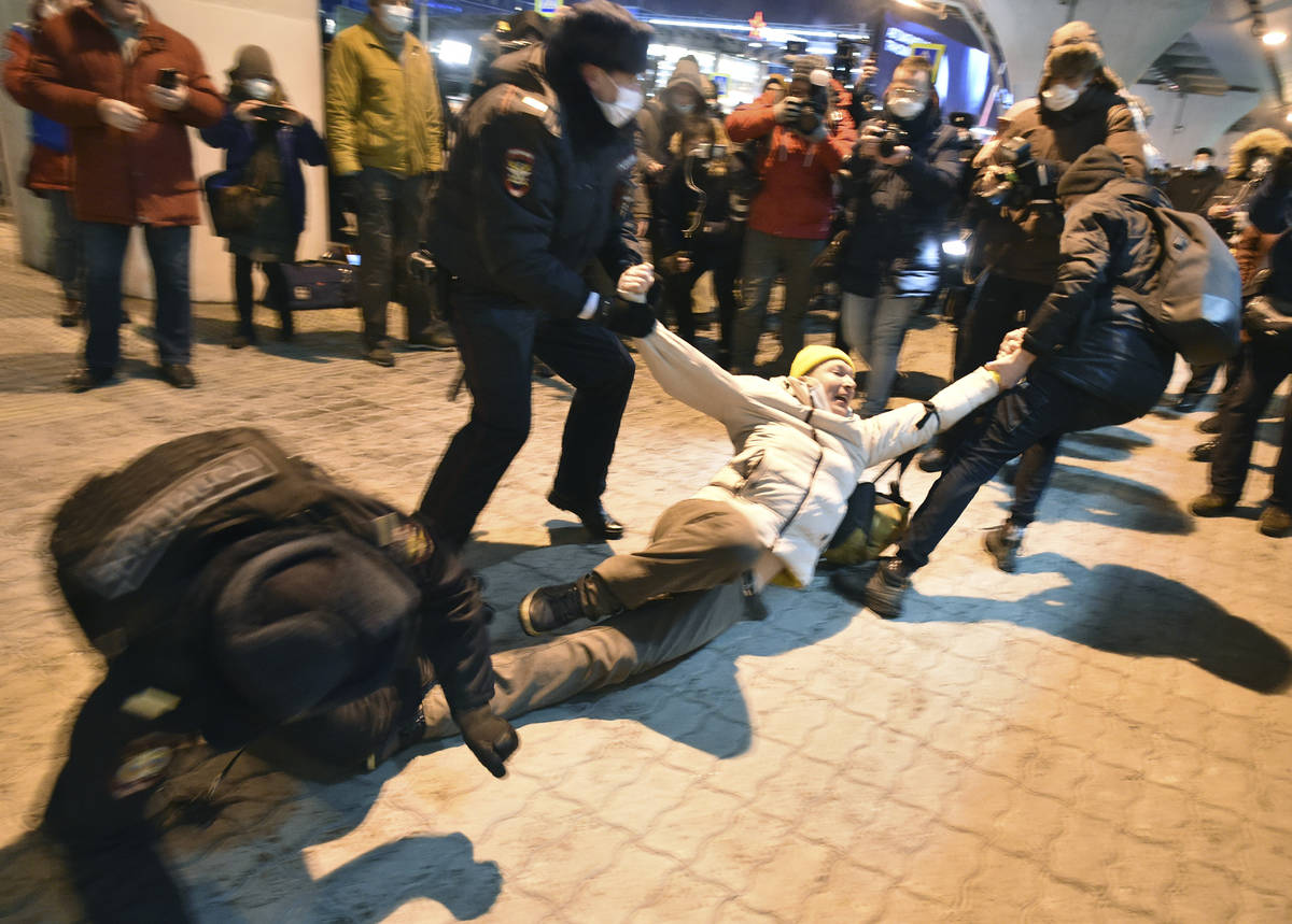 Police officers detain a man at Moscow's Vnukovo airport where Russian opposition leader Alexei ...