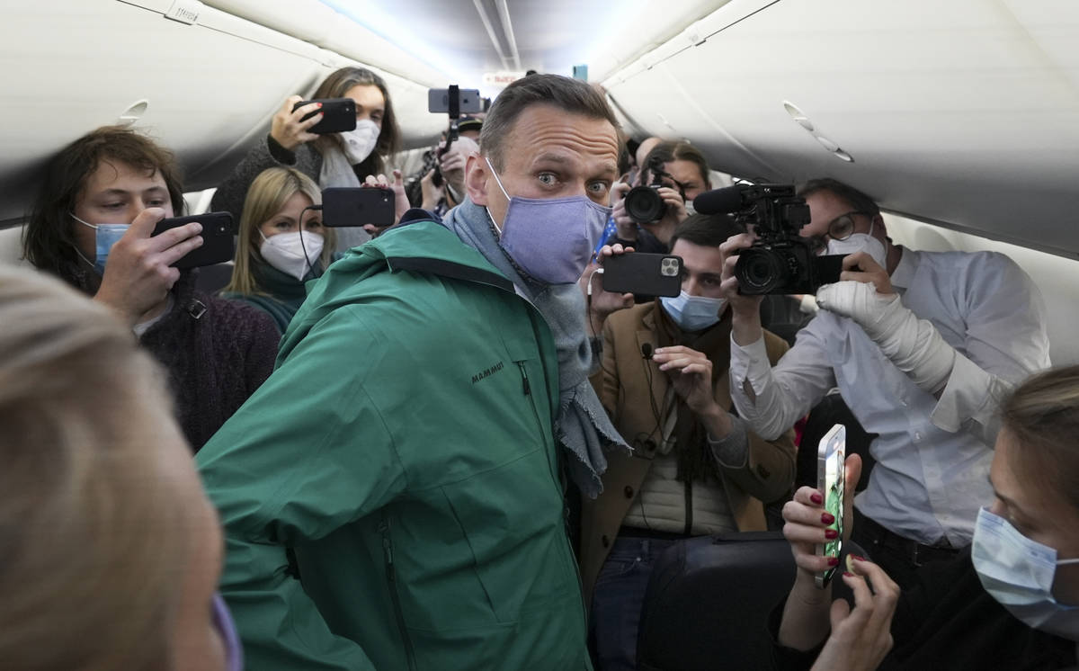 Alexei Navalny is surrounded by journalists inside the plane prior to his flight to Moscow in t ...