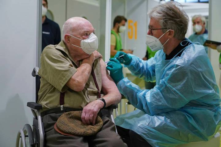 A doctor inoculates Herri Rehfeld, 92, against the new coronavirus with the Pfizer/BioNTech vac ...