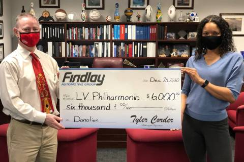 Findlay Automotive Group CFO Tyler Corder presents a check to Findlay human resources manager a ...