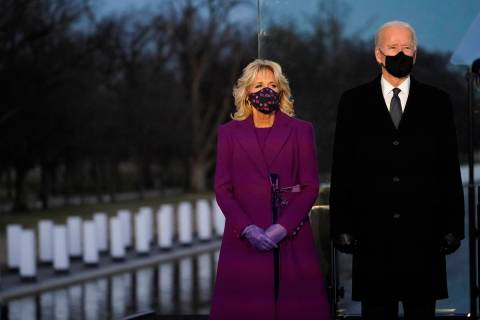 President-elect Joe Biden and Jill listen during a COVID-19 memorial, with lights placed around ...