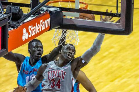 UNLV Rebels forward Cheikh Mbacke Diong (34) battles about the glass with New Mexico Lobos guar ...