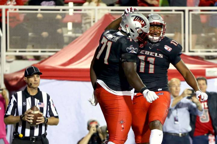 UNLV Rebels offensive lineman Justice Oluwaseun (71) celebrates a touchdown by teammate tight e ...