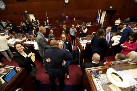 Assembly Speaker Jason Frierson, D-Las Vegas, hugs Sarah Peters, D-Reno, as female lawmakers wa ...