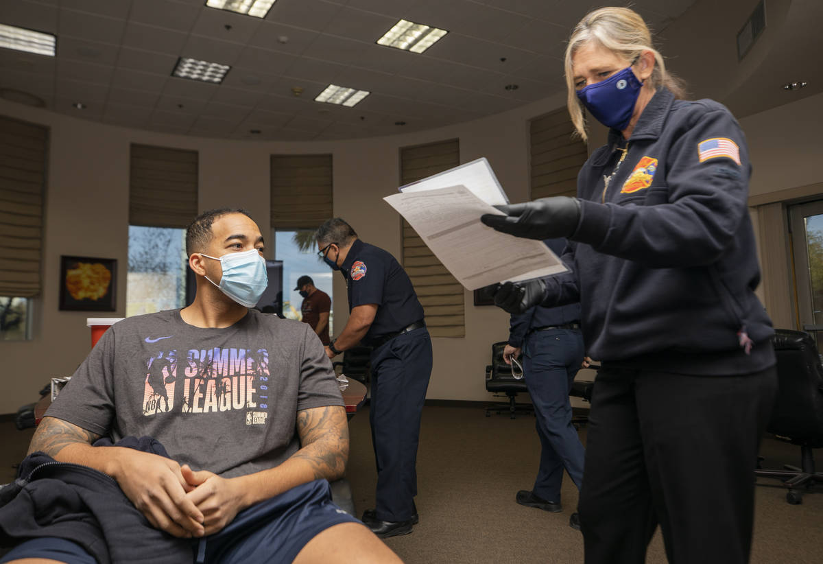 North Las Vegas firefighter Mike Rodgers, 31, left, prepares to receive a COVID-19 vaccine from ...