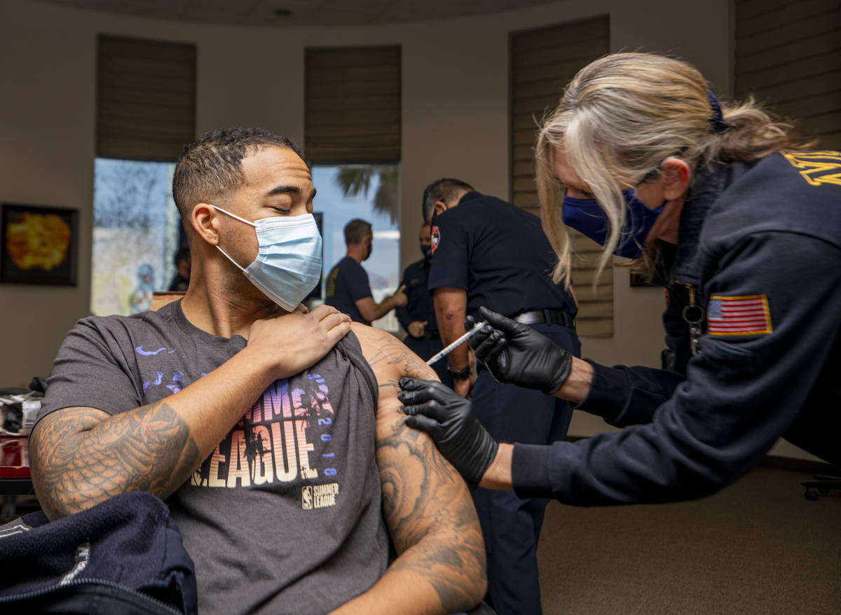 North Las Vegas firefighter Mike Rodgers, 31, left, is administrated a COVID-19 vaccine from em ...