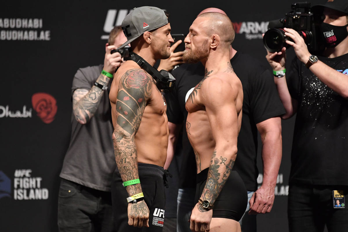 Opponents Dustin Poirier, left, and Conor McGregor of Ireland face off during the UFC 257 weigh ...