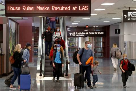 Masked travelers walk through Terminal 1 at McCarran International Airport in Las Vegas Friday, ...