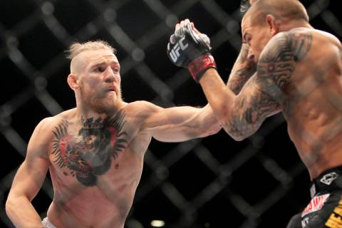 Conor McGregor hits Dustin Poirier with a left during their fight at UFC 178 Saturday, Sept. 27 ...