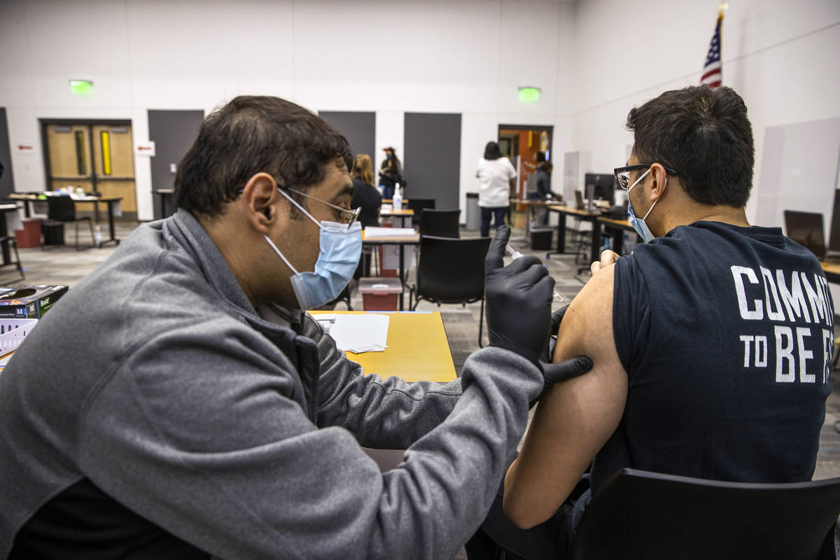 Hugo Peredo, left, with the UNLV School of Medicine, gives a COVID-19 vaccination to CSN studen ...