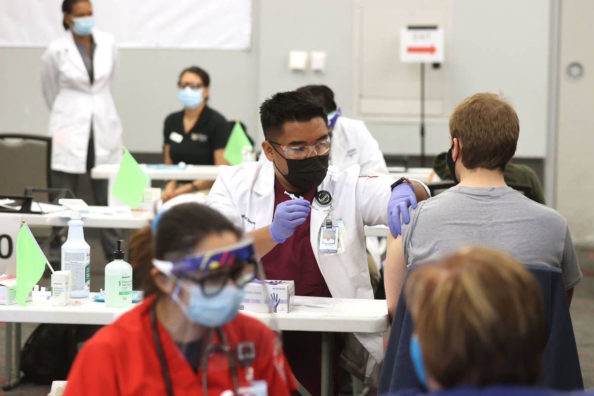 Medical student Michael Briones gives a COVID-19 vaccine during a UNLV Medicine clinic in the S ...