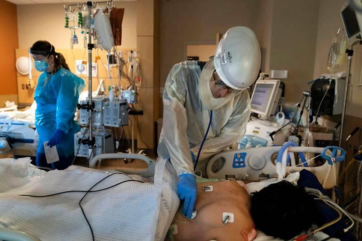 FILE - In this Nov. 19, 2020, file photo, Dr. Rafik Abdou checks on a COVID-19 patient at Provi ...