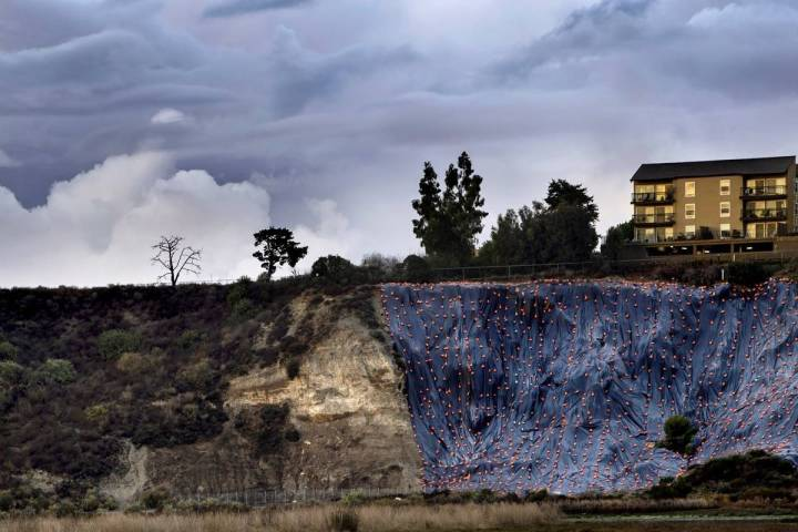 Newport Beach braces for rain as a hill in the Back Bay is covered with tarp on Saturday, Jan. ...