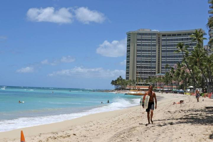 A surfer walks on a sparsely populated Waikiki Beach in Honolulu in June 2020. (AP Photo/Audrey ...